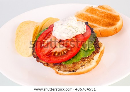 Dollop of sour cream and dill spread on turkey burger sandwich with sliced tomato and lettuce.