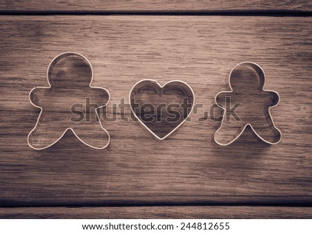 Dolls and heart shape of cookie cutters place on wood background with vignette, retro and sepia tone image, happy wedding anniversary and valentine's day symbol - stock photo