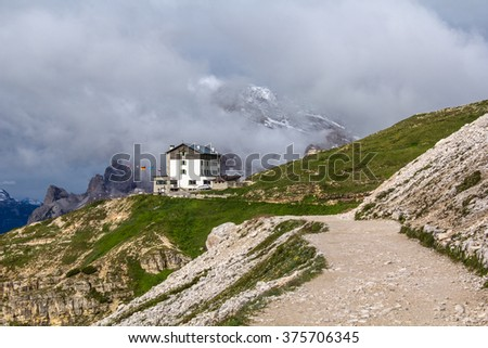 dolomite mountain landscape with a mountain cabin and a road on a sunny afternoon