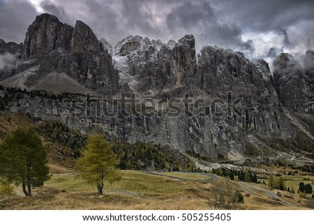 Dolomite Mountains and Forest over dramatic sky. Dolomites, Italy, Europe.
