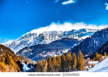 Dolomite mountains covered with white snow and green conifers in Italy - stock photo