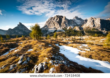 Dolomiti peaks and meadow with first autumn snow - stock photo
