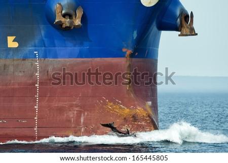 dolphin jumping near big ship bow - stock photo