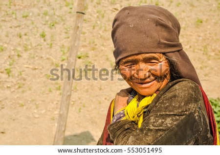 Dolpo, Nepal - circa May 2012: Old native woman with wrinkled face and brown headcloth looks down and smiles nicely in Dolpo, Nepal. Documentary editorial.