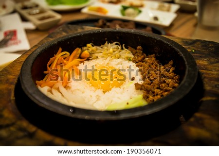 Dolsot bibimbap with fried egg, meat, vegetables and rice in a heated stone bowl.  Korean food. - stock photo