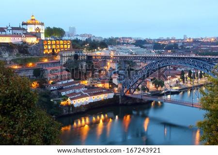 Dom Luis Bridge (Ponte Luis I) and Vila Nova de Gaia with popular wine caves in the evening, Porto, Portugal  - stock photo