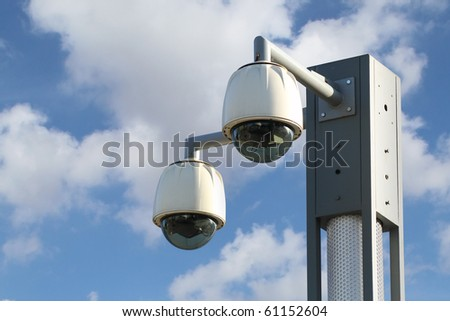 Dome CCTV  camera against the blue sky - stock photo