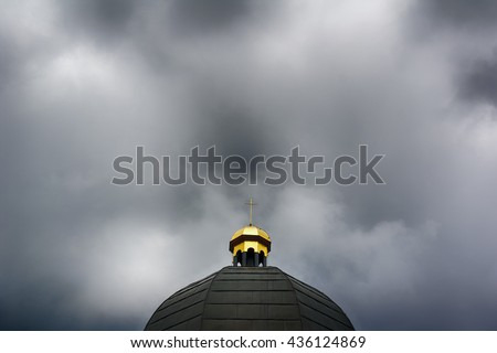 Dome of church / chapel with spire and cross as christian symbol. Stormy cloudy sky as metaphor of crisis of christianity (secularism, islamization, atheism, controversial scandals), dark exposure - stock photo