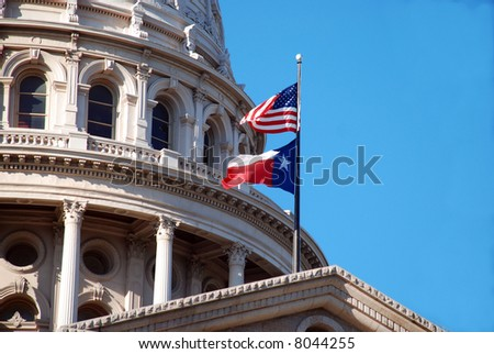 Dome of the Texas State capitol with its state and federal flags - stock photo