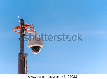 dome security camera against the blue sky - stock photo