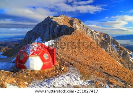Dome shaped shelter on sunny mountain ridge in autumn - stock photo
