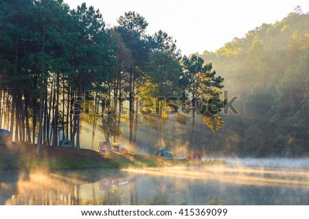 Dome tents beside the lake in the mist at sunrise at Pang Ung (Pang Tong reservoir), Mae Hong Son province, Thailand - stock photo