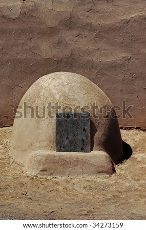 "domed ovens called ""hornos sits outside an adobe and stucco home."