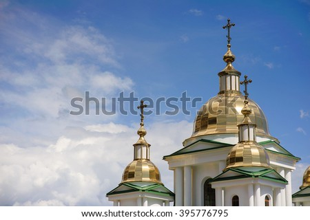 Domes of orthodox church on a background of blue sky and clouds