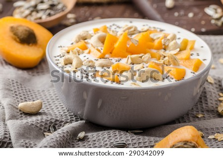 Domestic apricots musli yogurt with milk and crispy nuts and healthy seeds chia - stock photo
