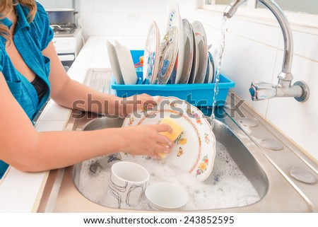 Domestic chores - Washing the dishes in the kitchen sink - stock photo