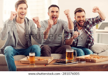 Domestic fans. Three happy young men watching football game and keeping arms raised while sitting on sofa - stock photo