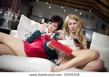 domestic life: 2 girls watching a romantic movie - stock photo