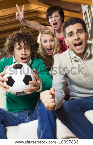 domestic life: group of friend watching soccer on tv - stock photo