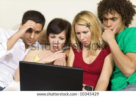 domestic life: group of friends having problems with computers - stock photo