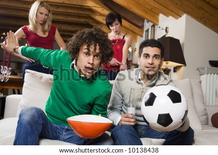 domestic life: group of friends watch soccer on tv while girlfriends stand behind. - stock photo