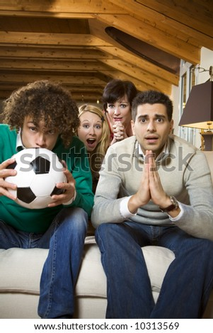 domestic life: group of friends watching a football match on tv
