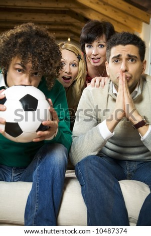 domestic life: group of friends watching a football match on tv - stock photo