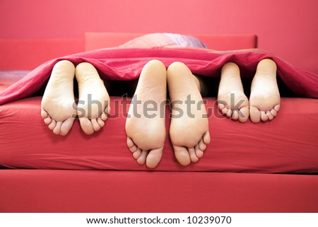 domestic life: threesome sharing the same bed - stock photo
