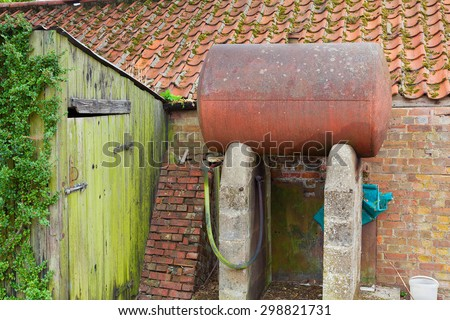 Domestic oil storage tank in a rusty state. - stock photo