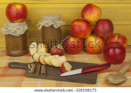 Domestic production of apple marmalade and cinnamon. Apple jam on the kitchen table. Processing autumn harvest of apples - stock photo