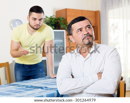 Domestic quarrel between senior father and young son  - stock photo