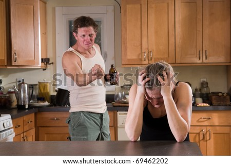 domestic violence - beer drinking man threatens his wife with fist - stock photo