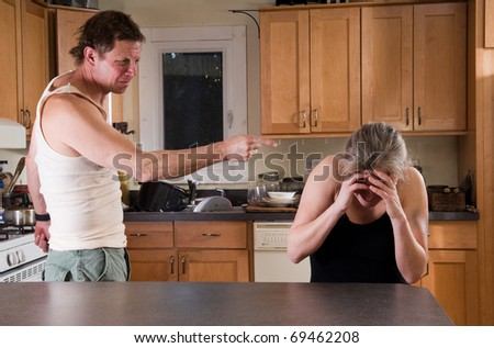 domestic violence - man threatens battered woman - stock photo