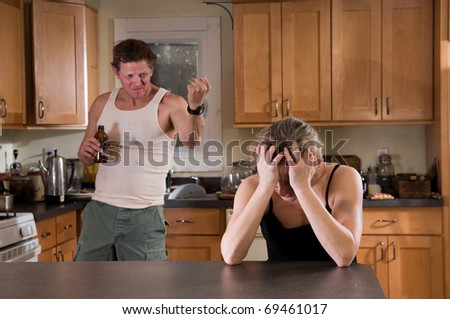 domestic violence - man (with beer) threatens woman, bruises on her arm - stock photo