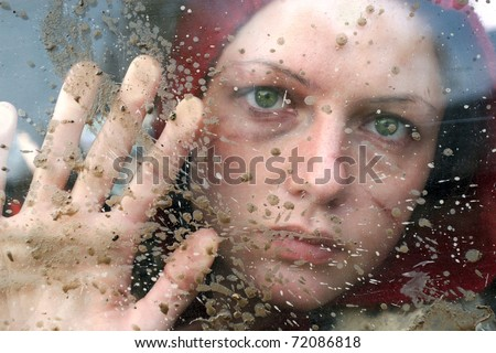 Domestic violence victim, a young  woman abused. Sight through  dirty  window.