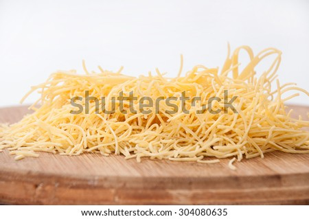Domestic yellow noodles on a kitchen board.