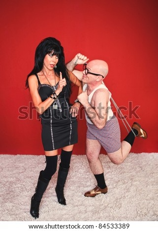 Dominatrix woman disapproves of her client's behavior in her dungeon. - stock photo