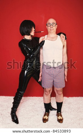 Dominatrix woman tightly grips a scared client in her dungeon. - stock photo