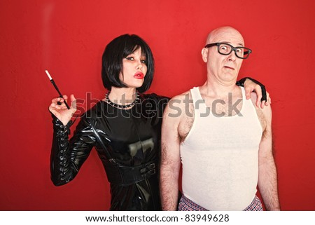 Dominatrix woman wraps her arm around fearful client. - stock photo