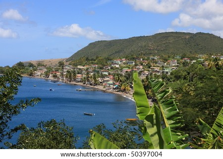 Dominica coastline with small town, hills and blue sky - stock photo