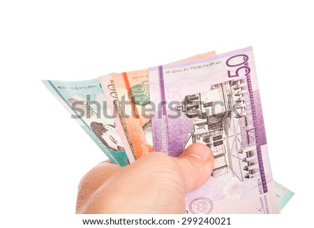 Dominican Republic money in a male hand, closeup studio photo isolated on white background
