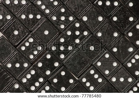 Domino cards fill a table. Diagonal view of tilled dominoes on a table - stock photo