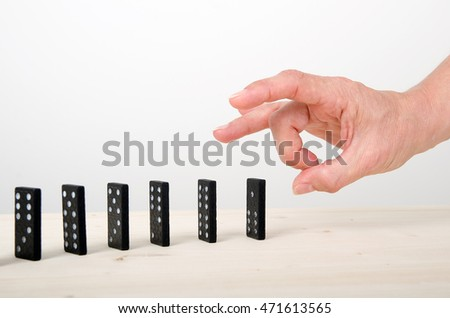 Domino effect - row of black dominoes about to fall after a woman flicks the first one over.