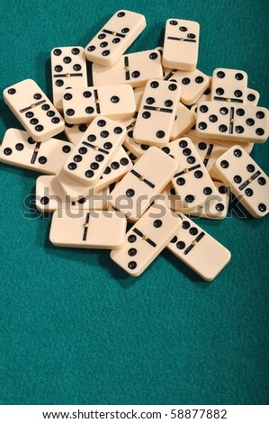 domino pieces on a green cloth background - stock photo