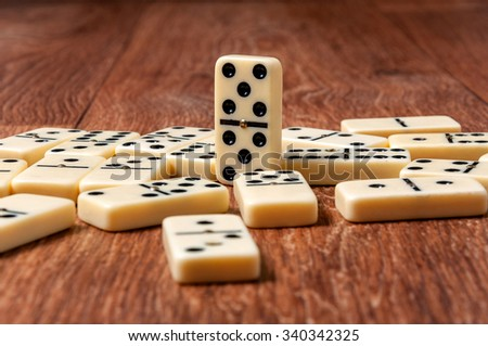 domino pieces on the brown wooden table background. - stock photo