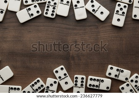 domino pieces on the brown wooden table with copy space - stock photo