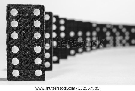 Domino row closeup with first one in focus on white background - stock photo