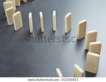 Domino's effect composition of a multiple domino bones placed in a row over the dark gray surface - stock photo