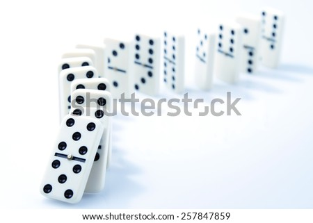 Dominoes on plain background, about to fall - stock photo