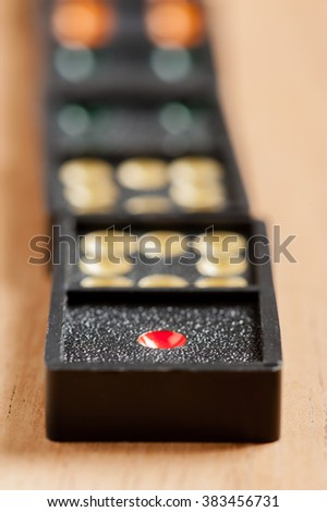 "Dominoes on wooden table. Dominoes is a game played with rectangular ""domino"" tiles."